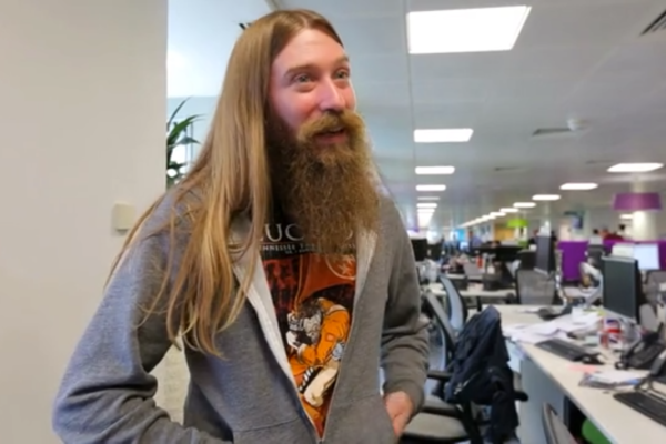 Man with long hair in an office giving an interview
