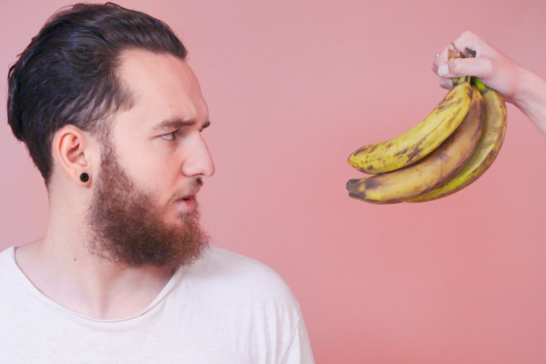 Man looking at bananas on a pink background