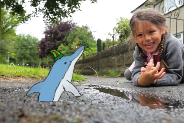 Young girl laughing on the sidewalk looking at an animation of a dolphin