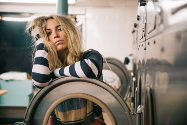 Woman looking bored and doing laundry
