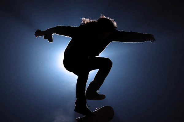 Man jumping on a skateboard in a dark place