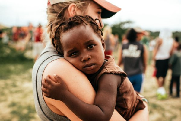 Woman holding a baby in a charity video