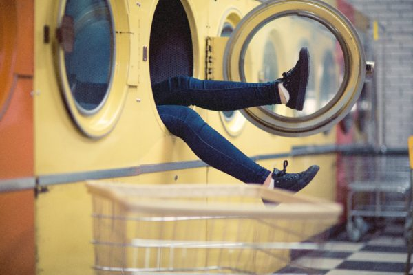 Woman's legs coming out of a washing machine