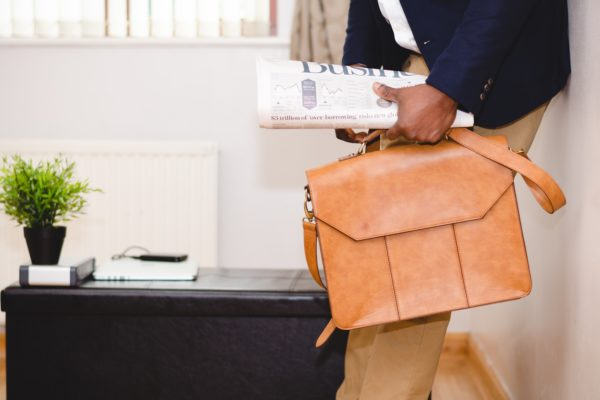 Business man holding the newspaper and a briefcase