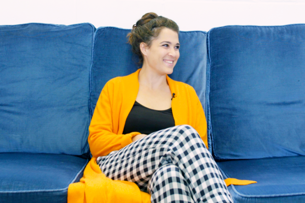 Woman dressed in yellow sitting on a blue couch and smiling