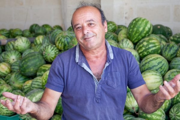 Man smiling in front of watermelons