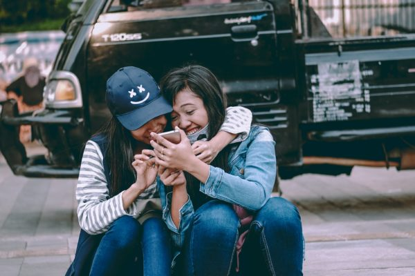 Two girls laughing and smiling on the sidewalk while looking at their phones