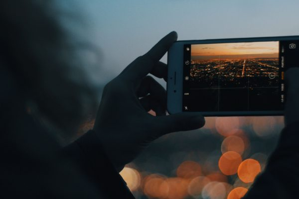 Woman taking a picture of city light on her phone