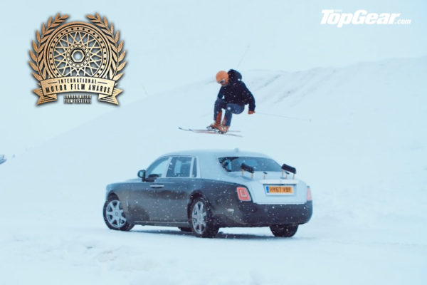 Man doing a jump over a car on skiis for Top Gear