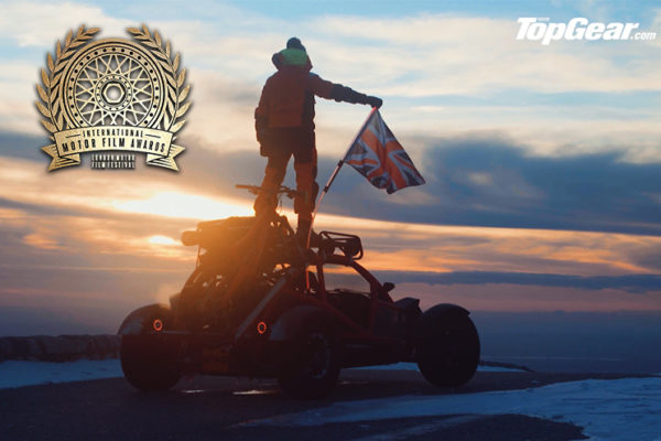 Top Gear Ariel Nomad standing on an extreme winter sports car and holding the UK flag
