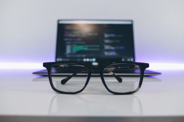 Glasses in front of a laptop which has code on it