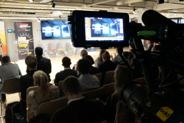 Behind the scenes camera filming at technological event