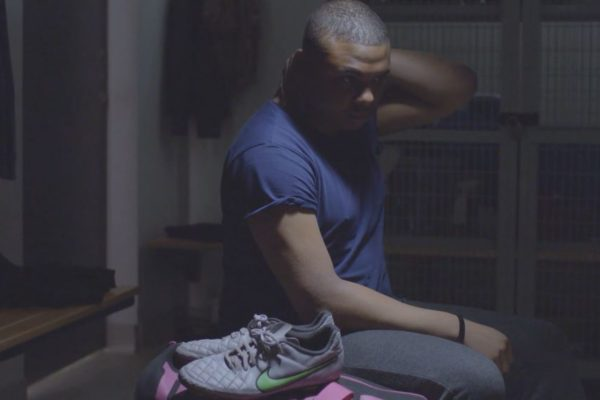 Man sitting on a bench in a locker for Young Minds Video made by Bold Content
