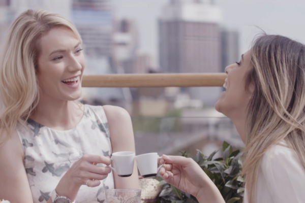 Two women laughing while clinking two small cups with espresso