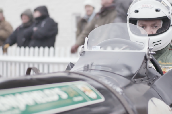 Man wearing a white helmet in a race car
