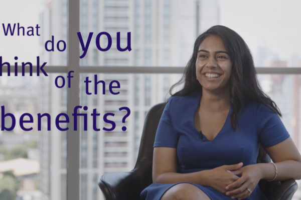 "Woman smiling in a chair and on-screen text reading ""What do you think of the benefits?'"