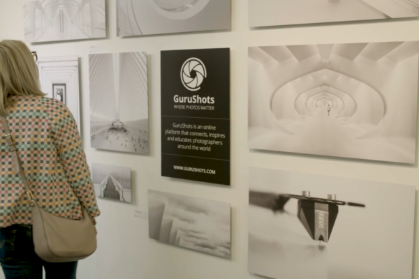 Woman looking at photographs on a wall from Bold COntent's video for Guru Shots