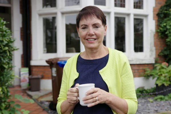 woman holding mug of tea in front of house