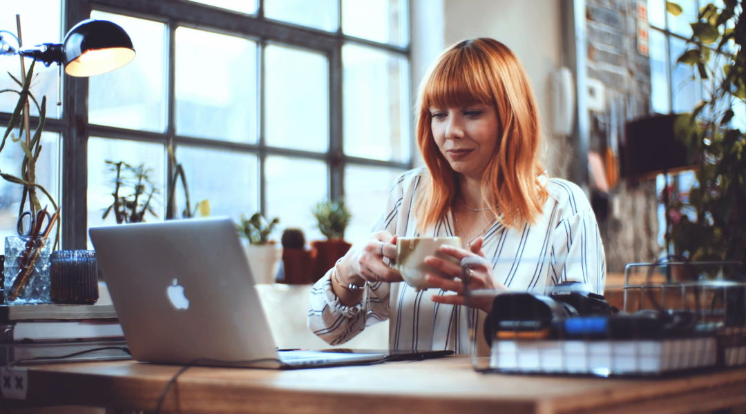 Lady drinking tea looking at laptop