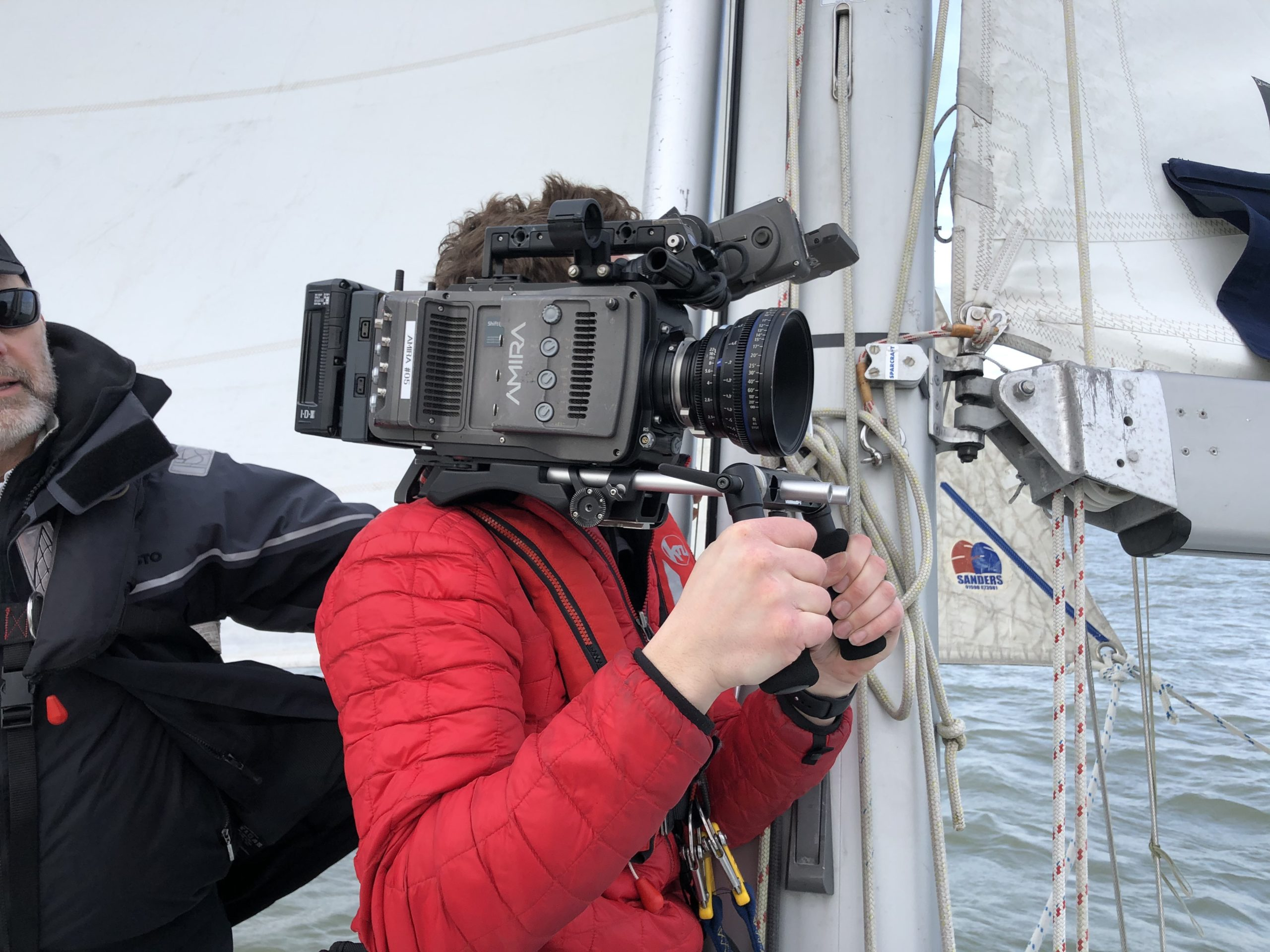 man filming on a boat holding a camera