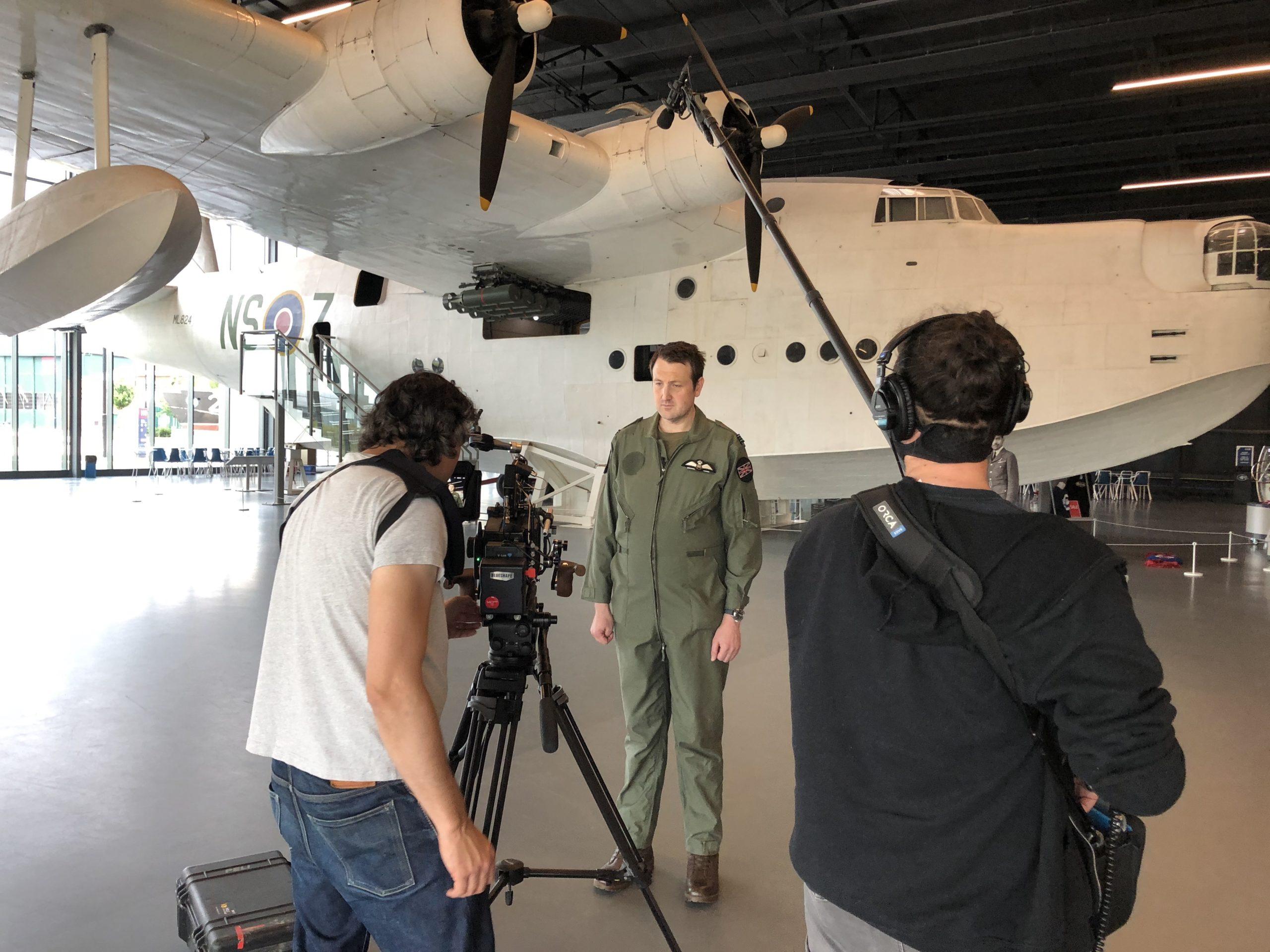 man being filmed in front of RAF plane