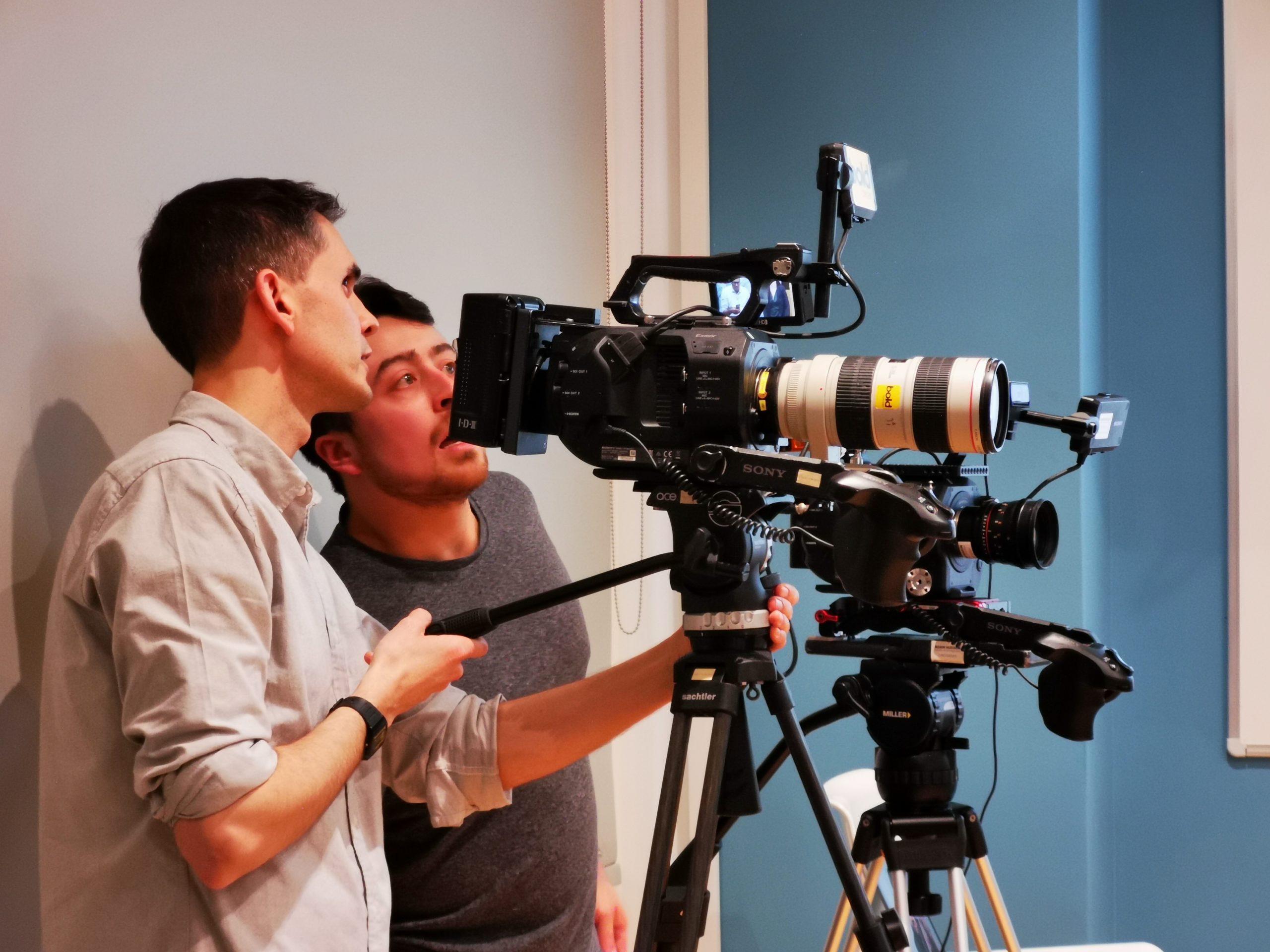 two cameramen using a camera on a shoot