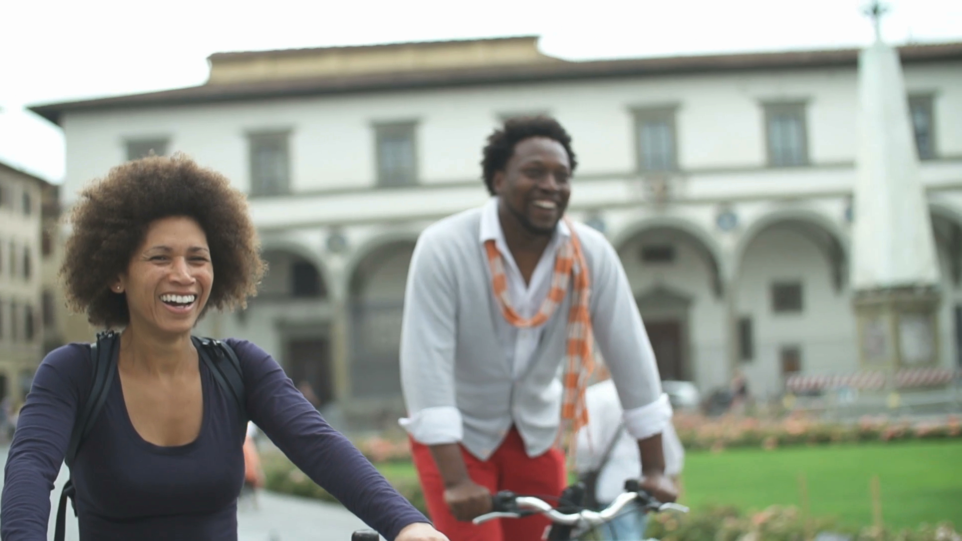 two people riding a bike in the city