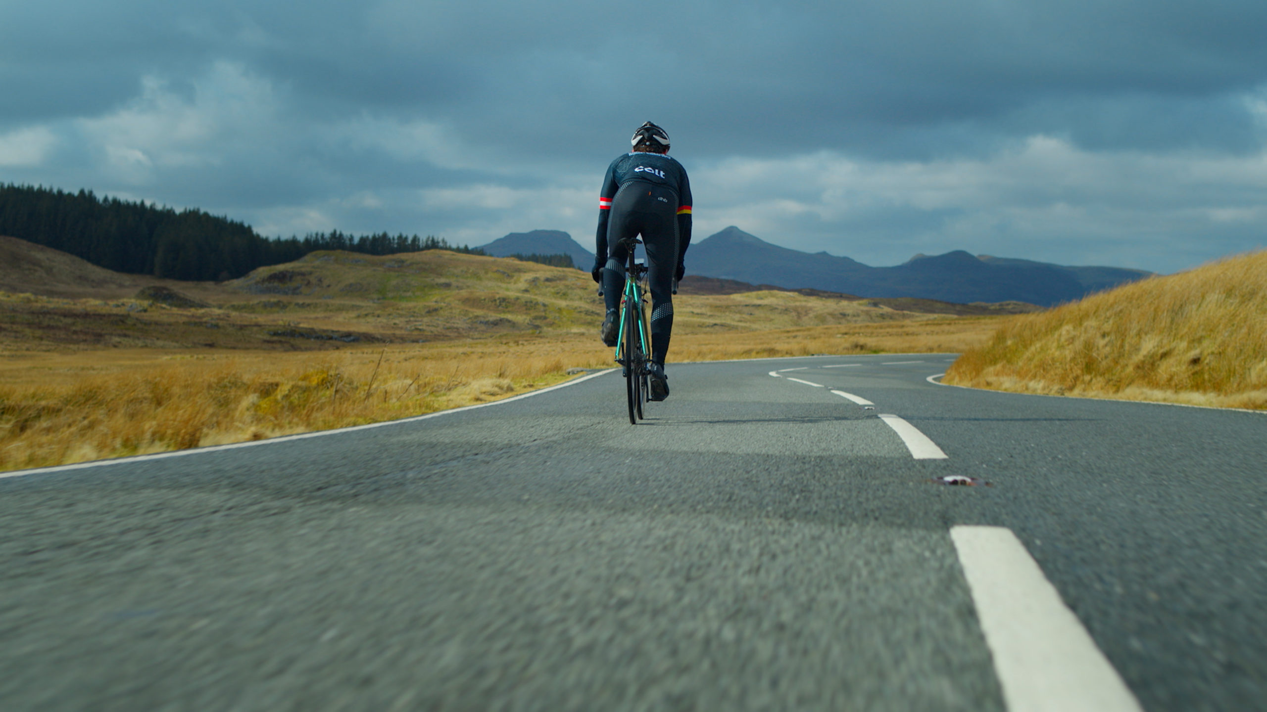the back of a man cycling on an empty road