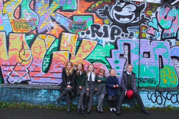 Children outside graffiti wall